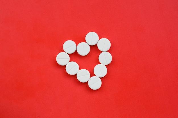 いくつかの白い錠剤はハートの形をした明るい赤の背景にあります。 Premium写真