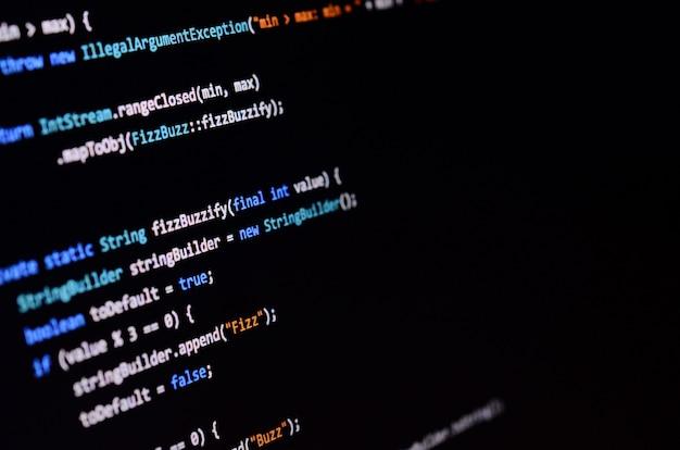 オフィスコンピューターのモニター上のコマンドラインのマクロ撮影。プログラマーの仕事の概念情報ラインの流れ Premium写真