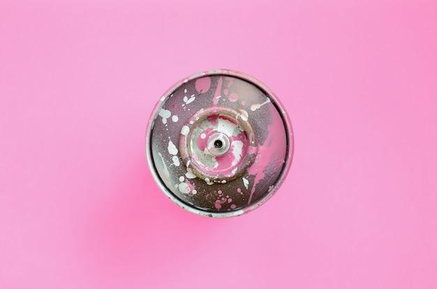 ピンクのペンキのしずくで使用済みスプレー缶は最小限の概念でファッションパステルピンク色の紙のテクスチャ表面にあります。 Premium写真