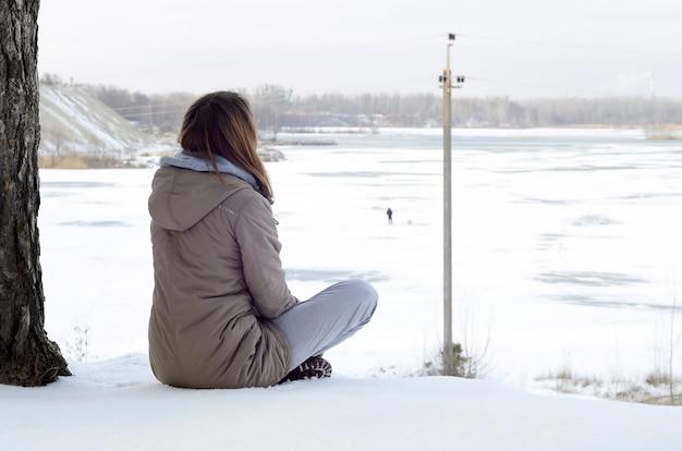 Молодая кавказская девушка в коричневом пальто смотрит вдаль на линию горизонта между небом и замерзшим озером зимой Premium Фотографии