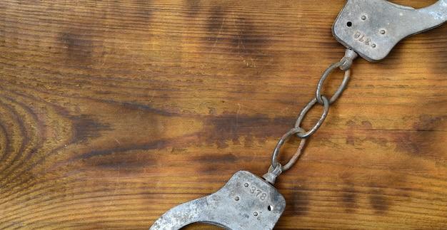古くてさびた警察の手錠は傷のついた木の表面にあります。古い犯罪の概念 Premium写真