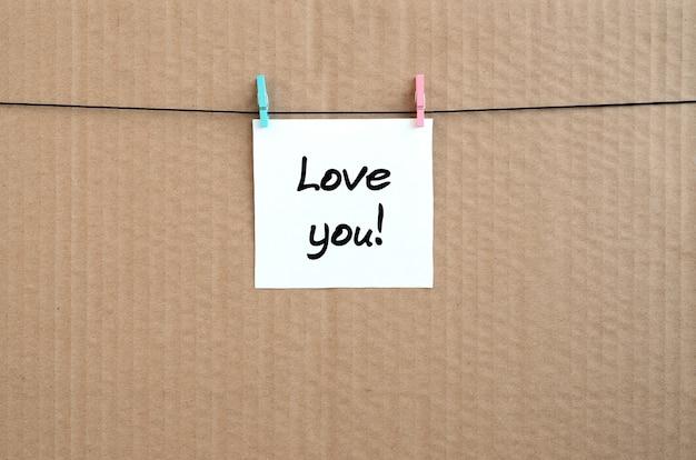 あなたを愛してます!茶色のボール紙の背景にロープに洗濯挟みで掛かる白いステッカーにメモが書かれて Premium写真