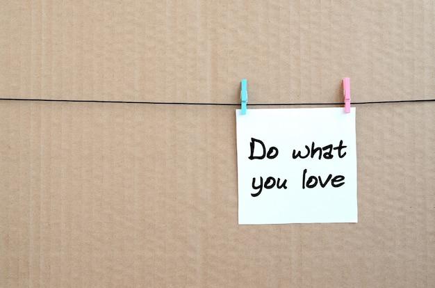 好きなことをしなさい。茶色のボール紙の背景にロープに洗濯挟みで掛かる白いステッカーにメモが書かれて Premium写真
