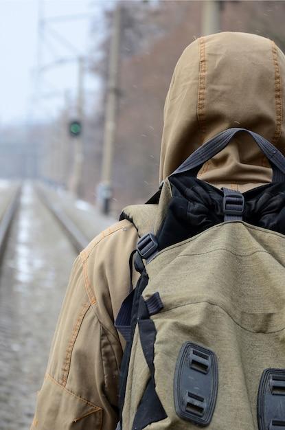 大きなバックパックを持った男が線路を進む Premium写真