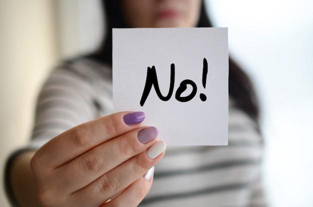 Молодая грустная девушка показывает белый стикер. кавказская брюнетка держит лист бумаги с сообщением. нет! Premium Фотографии