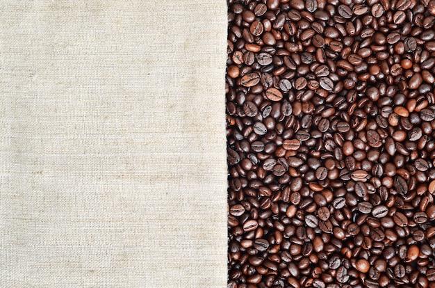 それにコーヒー豆と古くて粗い黄麻布で作られた灰色のキャンバスのテクスチャ Premium写真