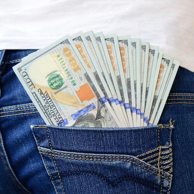 女の子のジーンズの後ろのポケットにたくさんのドル紙幣があります Premium写真