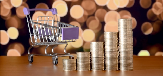 色付きのボケクリスマスライトの背景に成長グラフの空っぽのショッピングカートとお金のスタック Premium写真