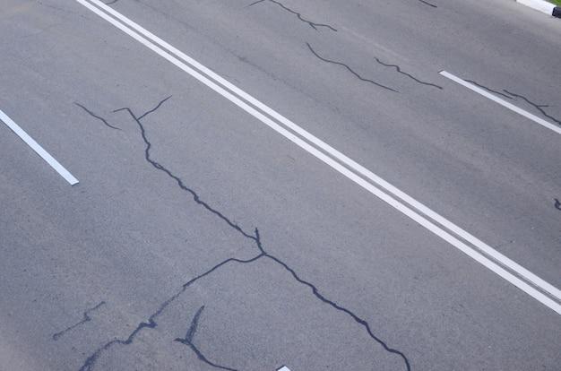 Повреждена плохая асфальтовая дорога с выбоинами. Premium Фотографии