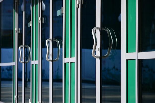 クロムドアハンドルと現代のアルミニウムオフィスファサードのガラス Premium写真