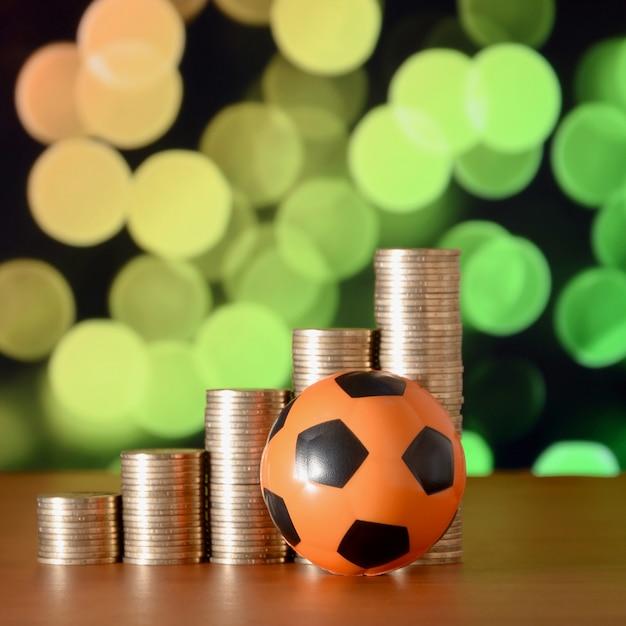 サッカーボールと成長グラフの黄金のコインのスタック Premium写真