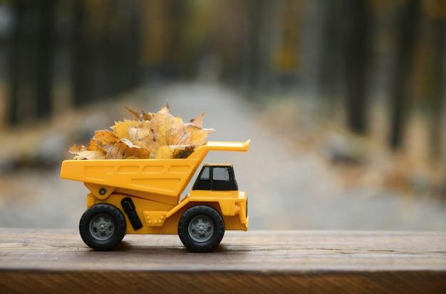 小さなおもちゃの黄色いトラックに黄色い落ち葉が積まれています。 Premium写真