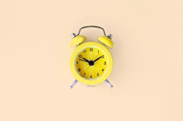 小さな黄色の目覚まし時計で新鮮なレモンスライス Premium写真