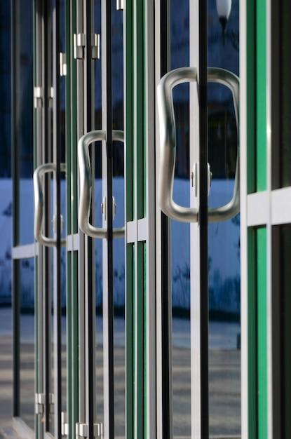 クロームドアハンドルとモダンなアルミニウムオフィスのファサードのガラス Premium写真
