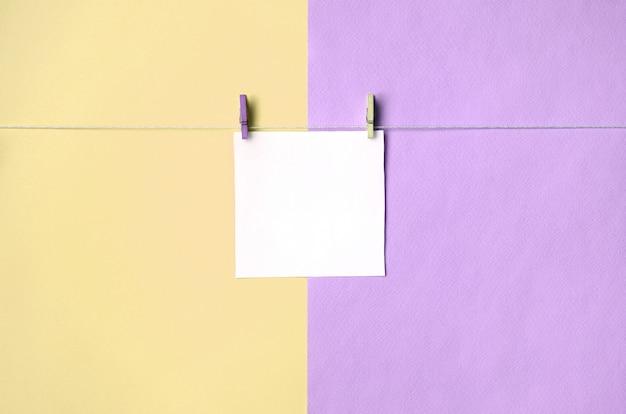 Кусок бумаги висит на веревке с колышками на фоне текстуры модных пастельных желтых и фиолетовых цветов Premium Фотографии