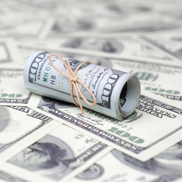 米ドルがロールアップされ、バンドで引き締められ、多くのアメリカの紙幣に横たわっています Premium写真