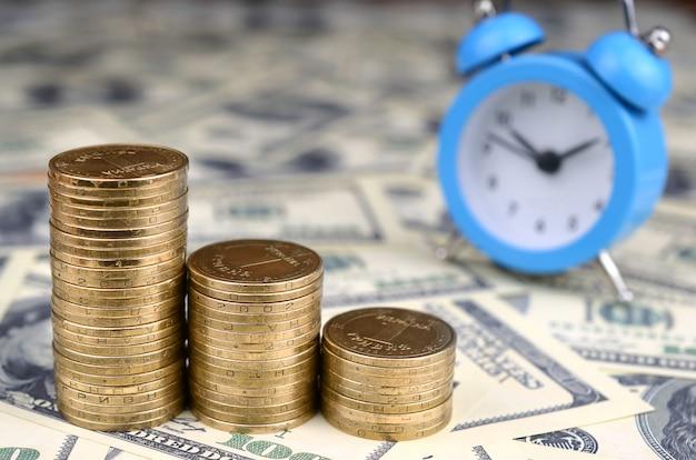 ぼやけた目覚まし時計と黄金のコインの山 Premium写真