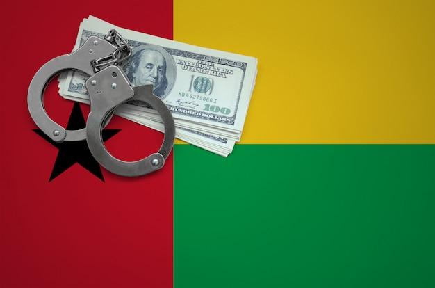手錠とドルの束とギニアビサウの旗。法律を破り、犯罪を犯すという概念 Premium写真