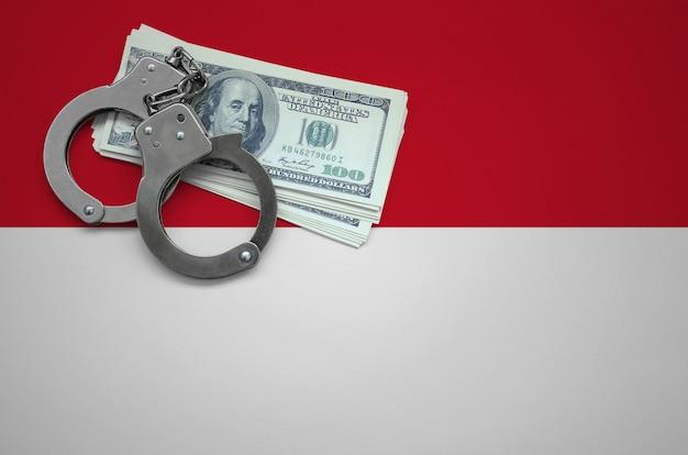 手錠とドルの束でインドネシアの国旗。法律を破り、犯罪を犯すという概念 Premium写真