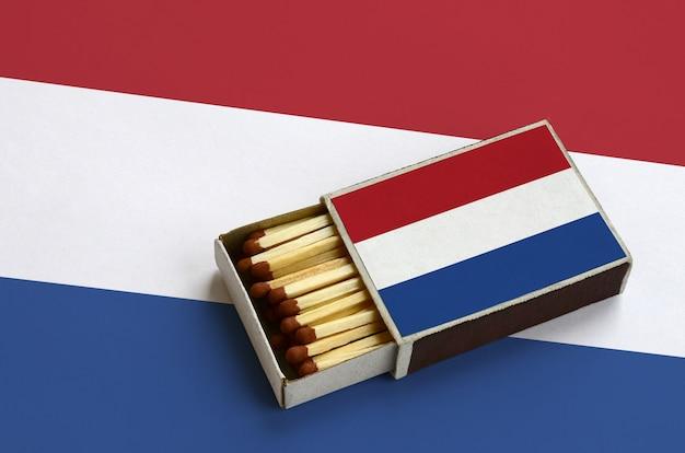 オランダの旗は、マッチで満たされ、大きな旗の上に横たわっている開いているマッチ箱に表示されます Premium写真