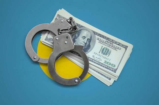 手錠とドルの束を持つパラオの国旗。国の通貨の腐敗。金融犯罪 Premium写真