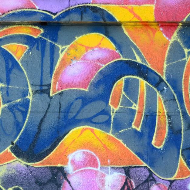 落書き図面の断片。ペイントで飾られた古い壁は、ストリートアート文化のスタイルで汚れています。温かみのある色調の背景テクスチャ Premium写真