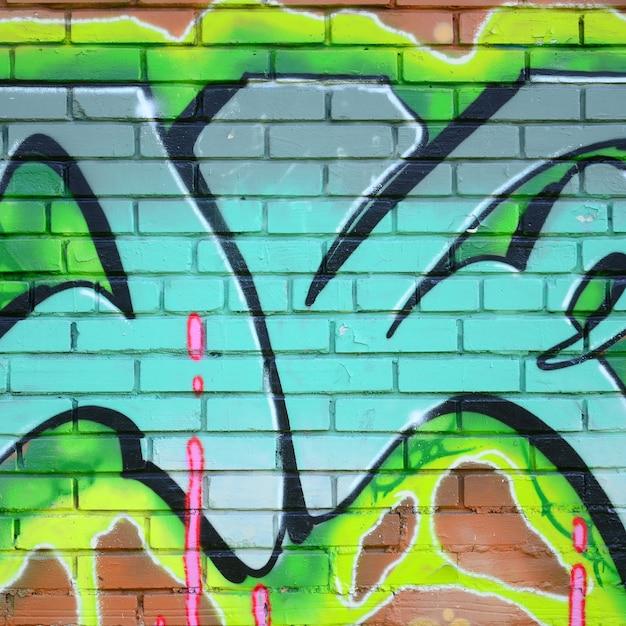 Фрагмент граффити рисунков. старая стена украшена краской пятна в стиле уличного искусства культуры. цветная текстура фона в зеленых тонах Premium Фотографии
