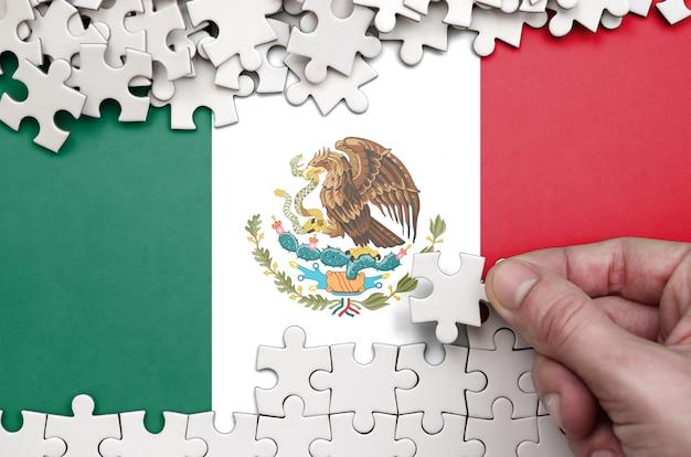 メキシコの旗は、人間の手が白い色のパズルを折るテーブルに描かれています Premium写真