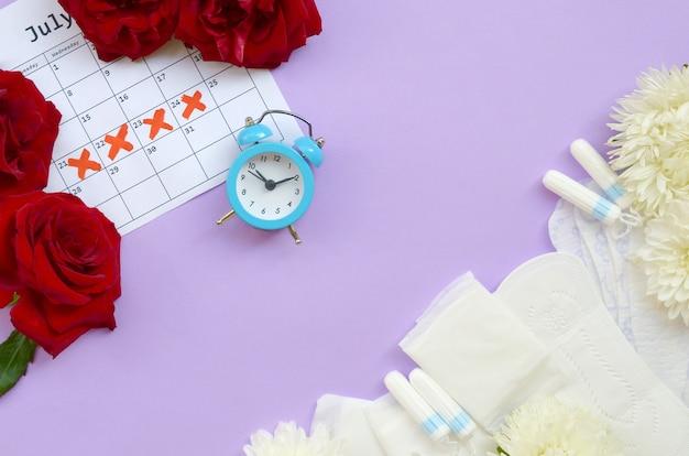 Менструальные прокладки и тампоны по календарю менструального периода с синим будильником и цветами красной розы Premium Фотографии