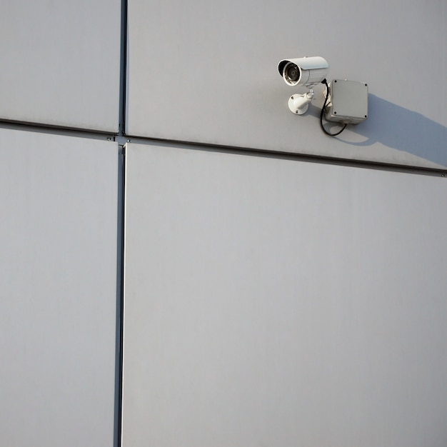 Белая металлическая камера наблюдения встроена в металлическую стену офисного здания Premium Фотографии