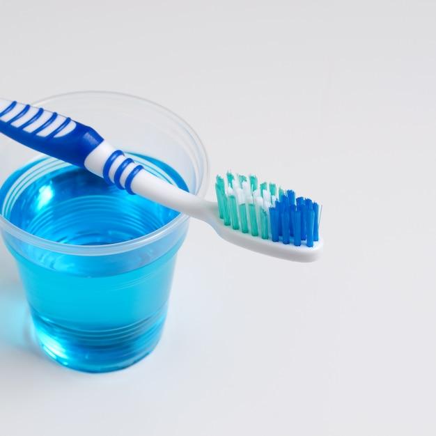 歯科衛生。歯ブラシ、うがい薬、白背景 Premium写真