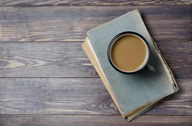 カバーが破れた古い本。ミルクコーヒー。木製の背景。フラットトップビュー Premium写真