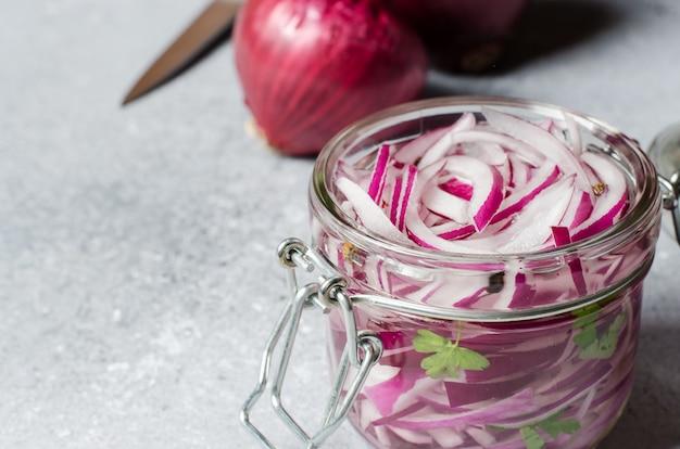 ガラスの瓶に酢で赤玉ねぎのみじん切り。肉や魚料理のおいしいおかず。ライトグレー Premium写真