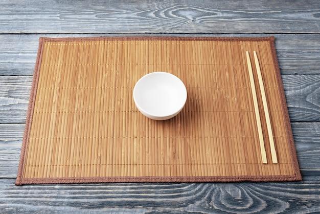 Две деревянные палочки для еды и белая чашка на бамбуковой циновке Premium Фотографии