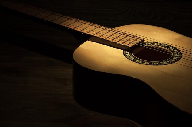 木製の織り目加工の背景の上に横たわるアコースティックギターに光線が当たる。 Premium写真