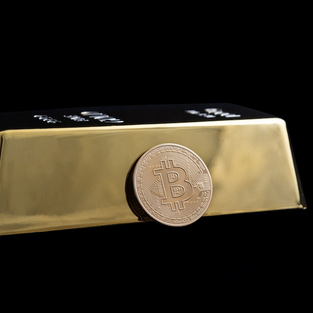 黒い背景にビットコインの暗号通貨と金の延べ棒。 Premium写真