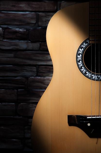 レンガの壁の背景に立っているアコースティックギターに光のビームが当たる。 Premium写真