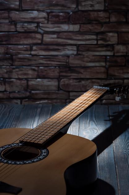 光のビームは、暗闇の中で横になっているアコースティックギターを照らします。 Premium写真