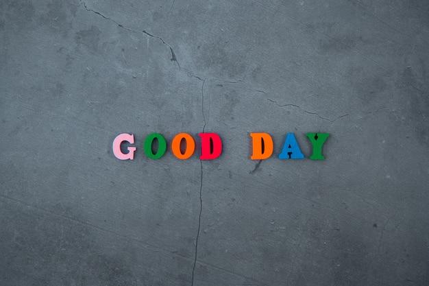 色とりどりの良い一日の言葉は灰色の漆喰壁の木の手紙で作られています。 Premium写真
