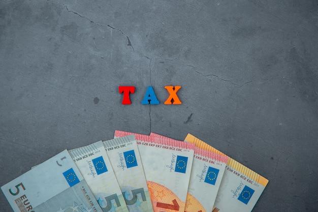 色とりどりの税の言葉は灰色の漆喰壁に木製の文字で作られています。 Premium写真