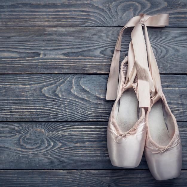 リボンの弓とトウシューズバレエダンスシューズは木の上の釘に掛かる。 Premium写真