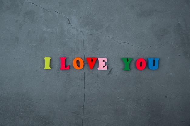 大好きな色とりどりの言葉は、灰色の漆喰の壁に木製の文字でできています。 Premium写真