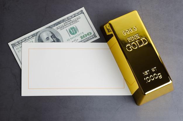 金の延べ棒地金ドル紙幣とグリーティングカード。 Premium写真