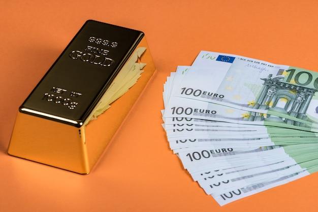 オレンジ色の表面にユーロの現金と金の延べ棒。紙幣。お金。ビル。インゴット。地金。 Premium写真