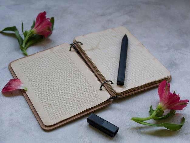 灰色の背景上の花と空白のノートブック Premium写真