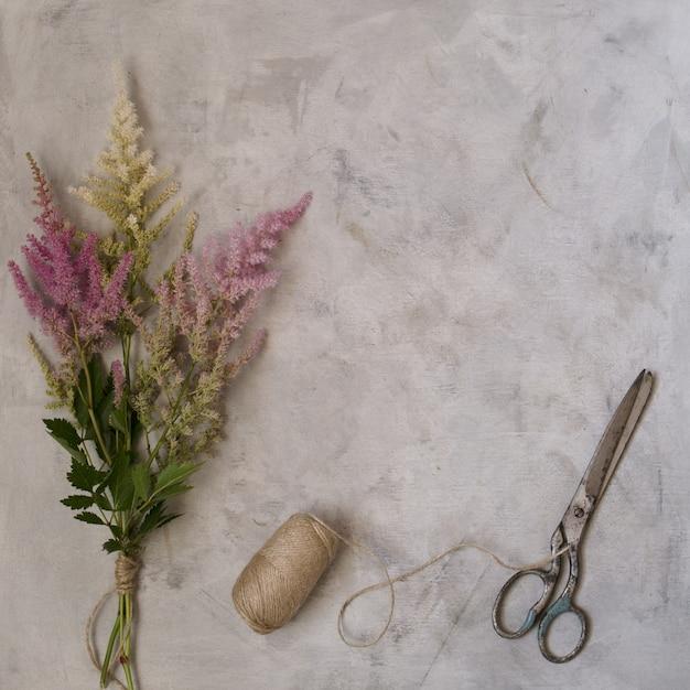 かわいいヴィンテージは、花、色とりどりのアスティルバ、古いはさみと灰色の背景にリネン糸でモックアップします。上面図、コピースペース Premium写真