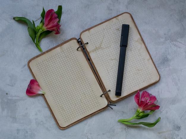 灰色の背景上の花と空白のノートブック。 Premium写真