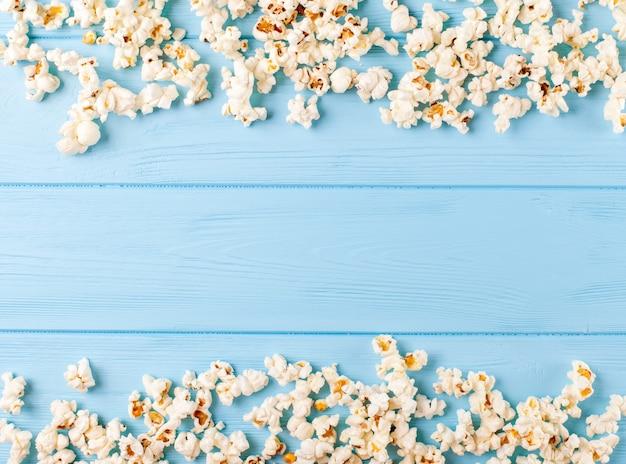 ポップコーンの水平方向のバナー。青い木製の背景にフレームの形で横になっているカーネル。 Premium写真