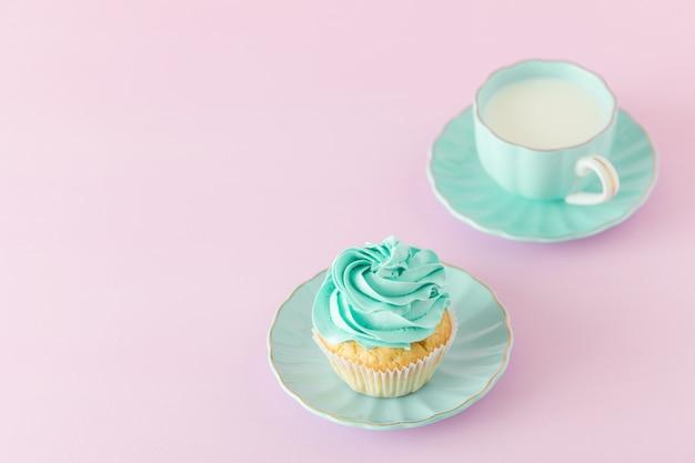 ミントクリームの装飾とコピースペースとピンクのパステル調の背景にミルクのカップケーキ Premium写真