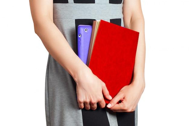 女性は白い背景の上のタブレットとノートを保持します。 Premium写真